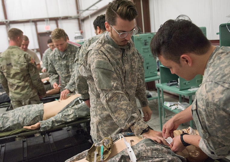 Two men in fatigues examining a manikin in a field hospital