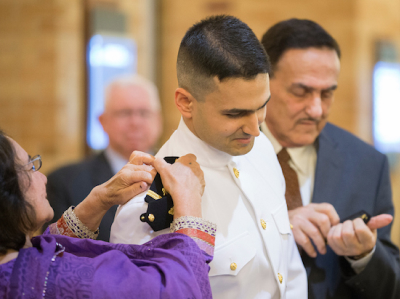 A medical student receiving his miliary commission. His parents putting his epaulets on his uniform